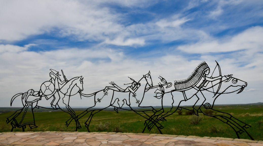 Stahlgestelle von drei Indianern auf Pferden vor grüner Wiese und blauem Himmel