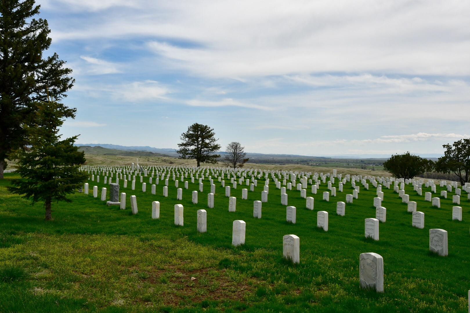 Weiße Grabsteine auf grüner Wiese mit Tannenbäumen, weiter Blick ins Land