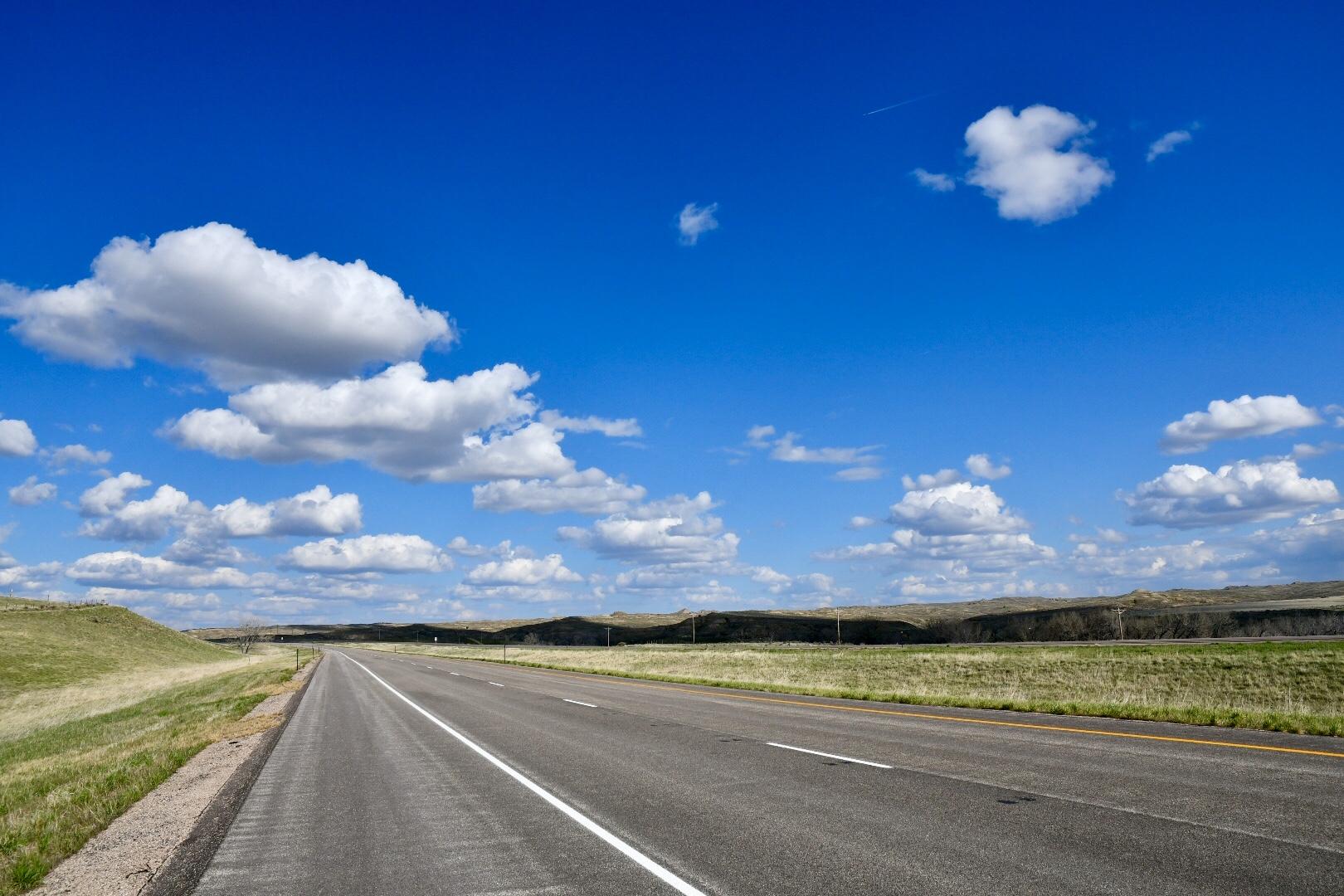 blauer Himmel, weiße Wolken, grüne Hügel, graue Straße - das ist Wyoming