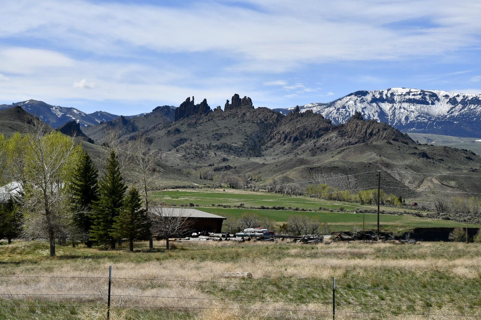 Farm im Shoshone National Forest mit grünem Weideland vor beeindruckender Bergkulisse mit gezackten Felsen