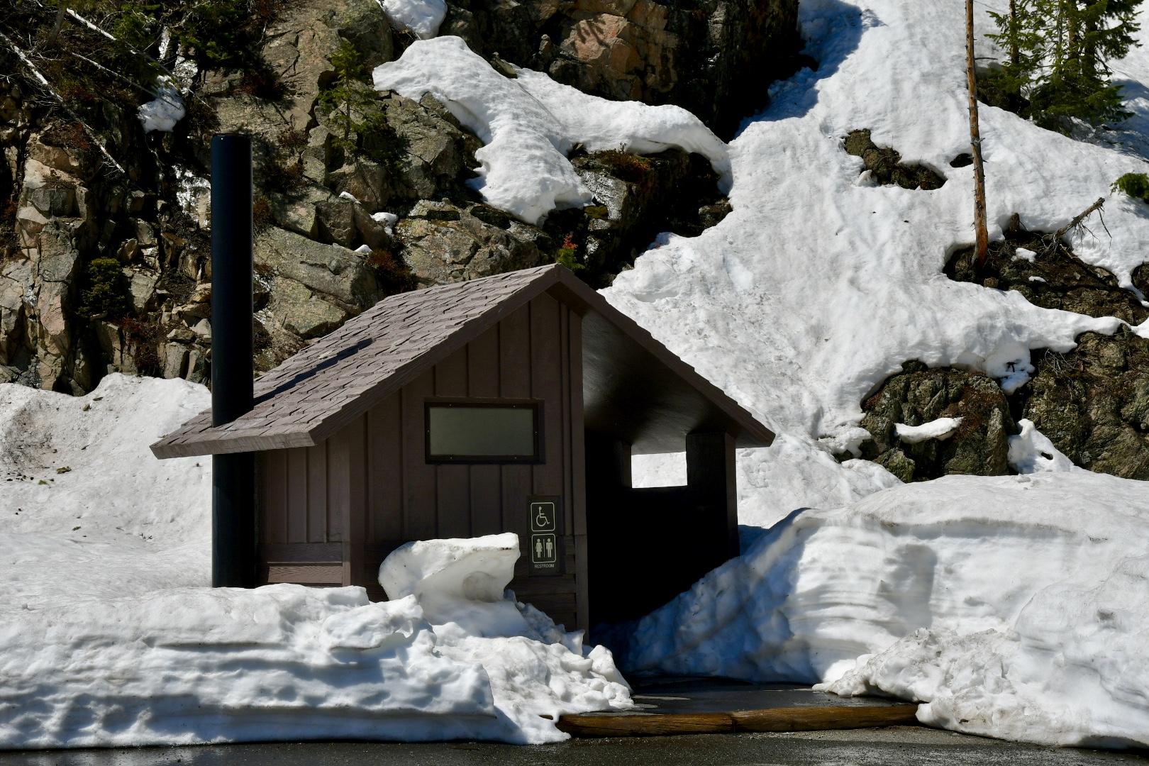 Kleines braunes Klohäuschen mit Satteldach vor Felswand wird von dicken Schneemassen eingerahmt