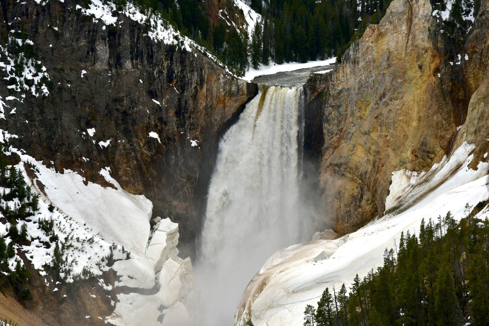 An Wasserfall, der an ockerfarbenen Felsen herunterstürzt, lösen sich Schneebretter links und rechts des Wasserfalls fast auf und stürzen jeden Moment auch in die Tiefe