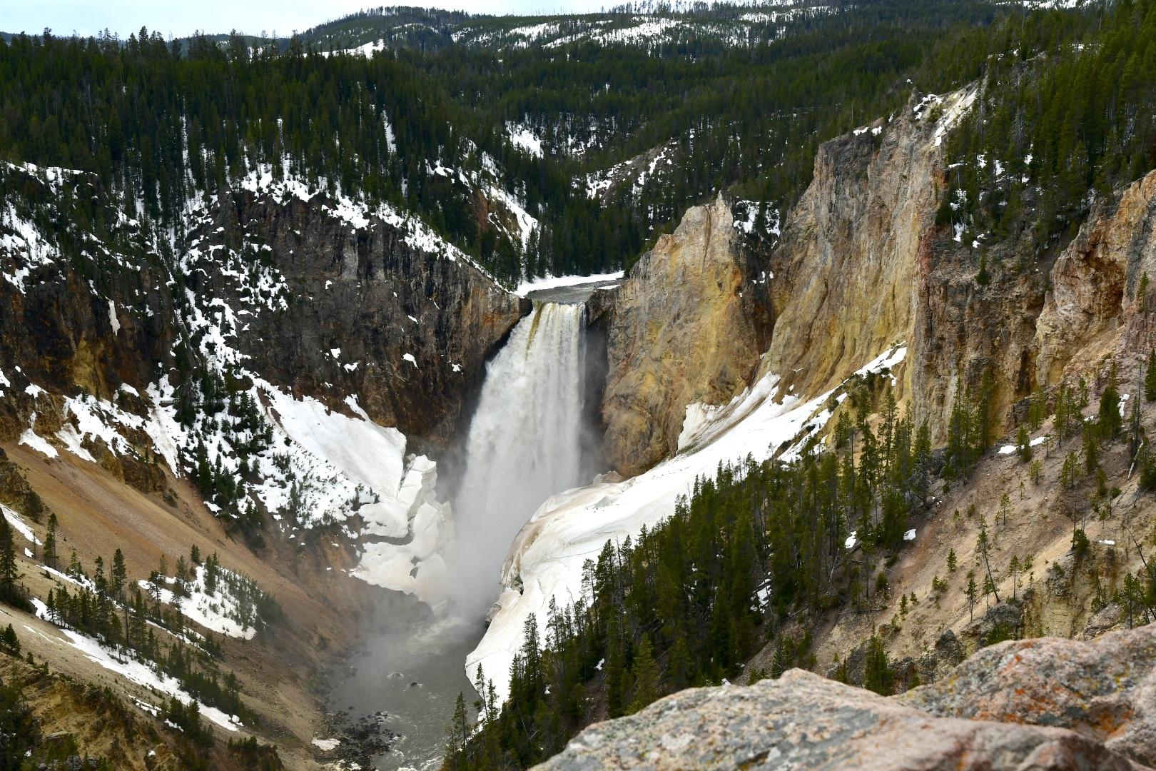 Wasserfälle im Yellowstone Nationalpark - Wasser fällt zwischen Schneebrettern und ockerfarbener Schlucht 100 Meter tief in einen Fluss