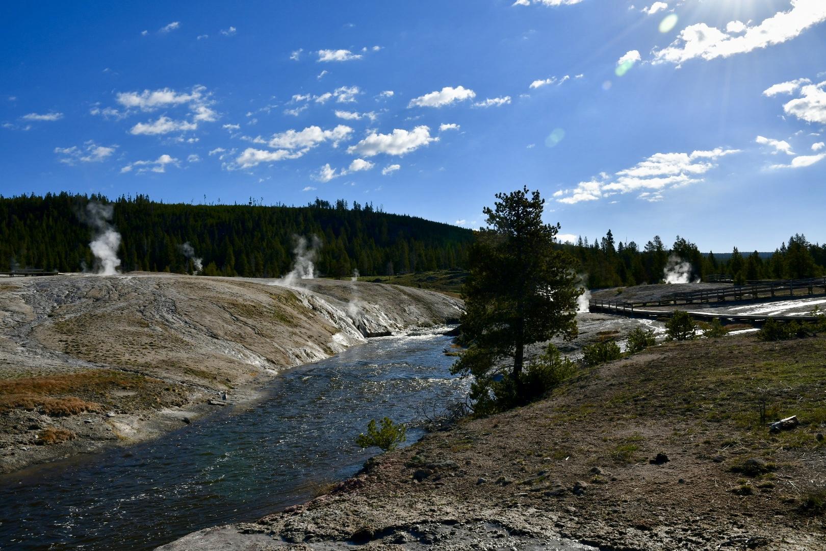 Auf Holzstegen geht man auf dem Old Faithful Rundweg vorbei an dampfenden Bächen, verätzter Erde und dampfenden Thermalbecken