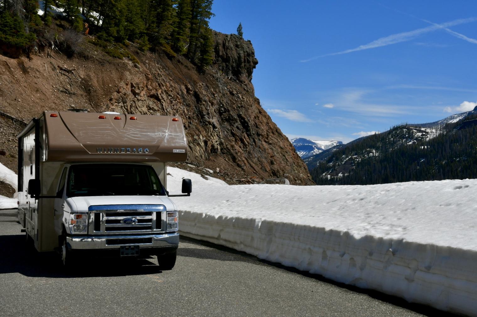 Wohnmobil auf von Schnee frei gefräßter Pass-Straße im Yellowstone Nationalpark